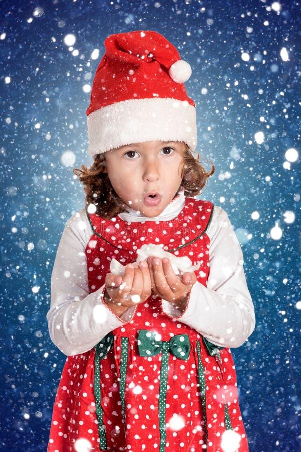 Bambina nel Natale che soffia i fiocchi di neve immagini stock libere da diritti