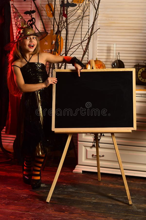 Bambina nel punto del cappello dello stregone al bordo dell'annuncio su Halloween Bambina in abito dello stregone con l'annuncio  immagine stock