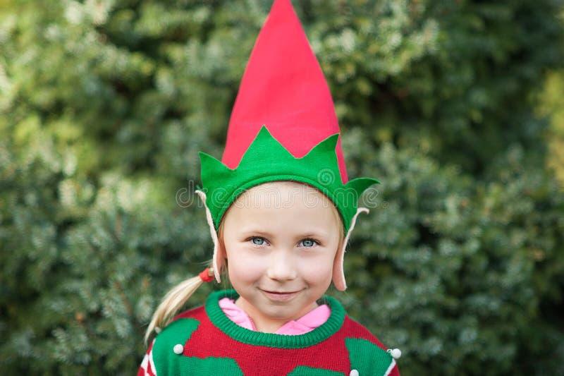Bambina nell'aspettare del maglione e del cappello dell'elfo Natale nel legno Ritratto di ritratto a mezzo busto di piccolo bambi fotografie stock libere da diritti