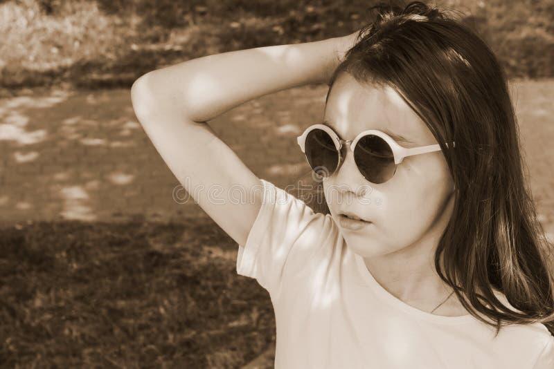 Bambina in occhiali da sole con capelli sciolti, tonificati immagine stock libera da diritti
