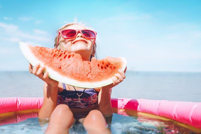 Bambina in occhiali da sole rosa con il ritratto divertente di grande segmento dell'anguria Immagine sana di concetto di cibo fotografie stock
