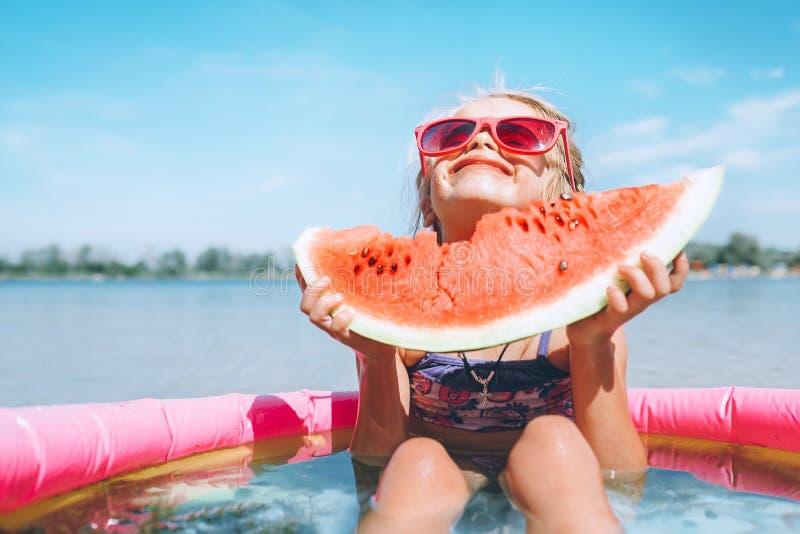Bambina in occhiali da sole rosa con il segmento offerto dell'anguria divertente immagini stock libere da diritti