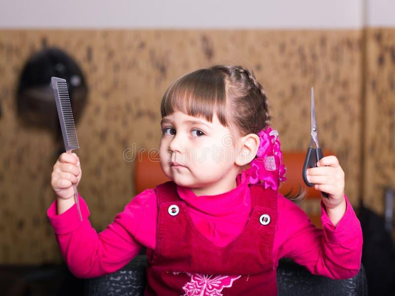 Bambina in parrucchiere con le forbici ed il pettine fotografia stock libera da diritti