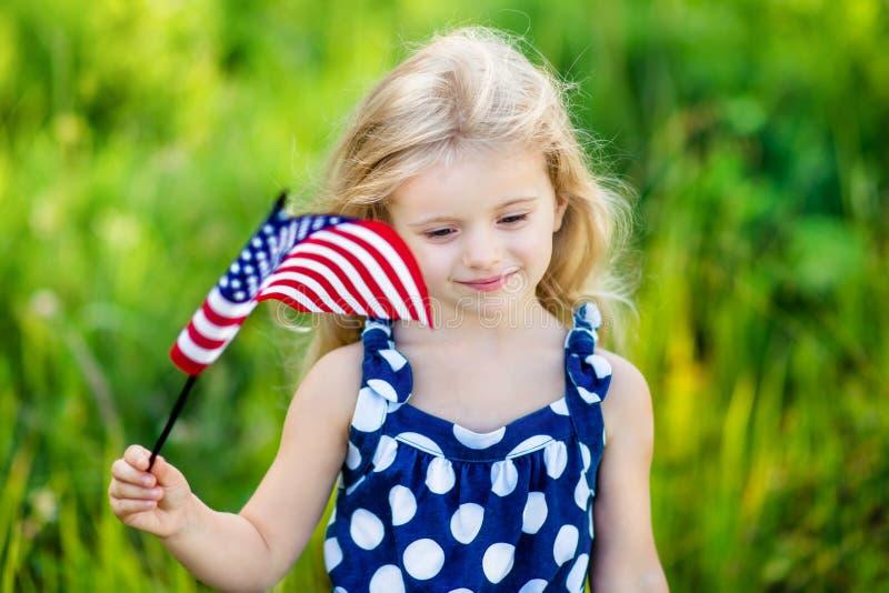 Bambina pensierosa con la bandiera americana lunga della tenuta dei capelli biondi fotografia stock libera da diritti