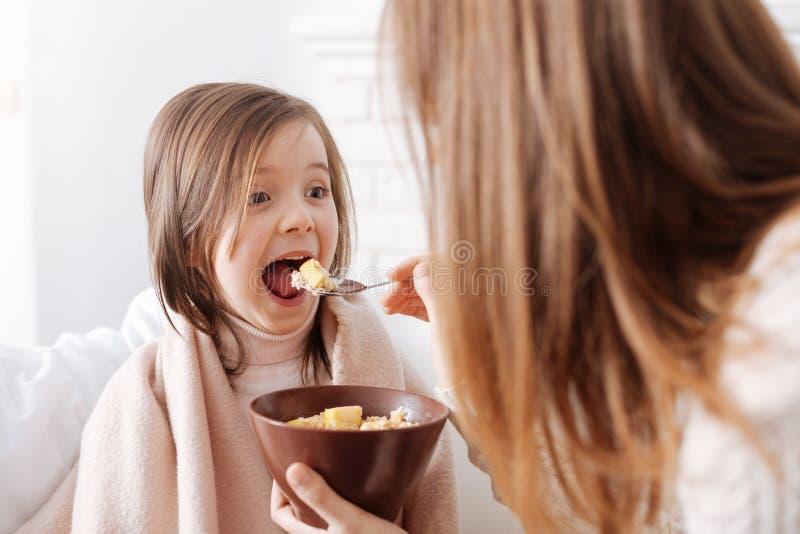 Bambina piacevole allegra che gode della prima colazione con la madre immagine stock libera da diritti