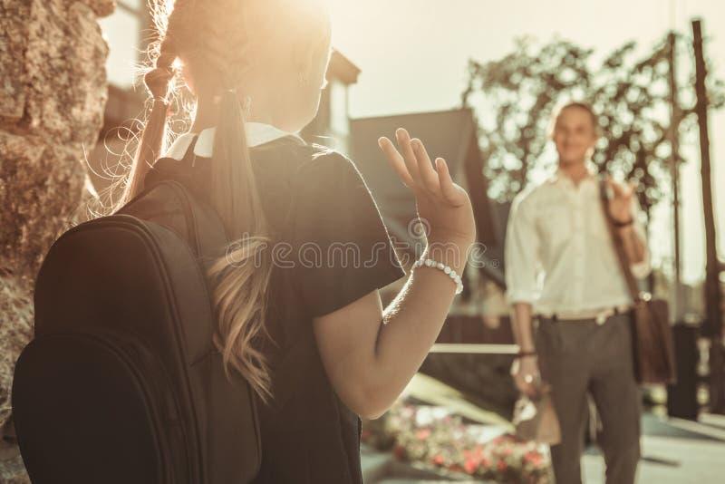 Bambina piacevole con la mano d'ondeggiamento dei capelli lunghi mentre andando via di casa fotografia stock libera da diritti