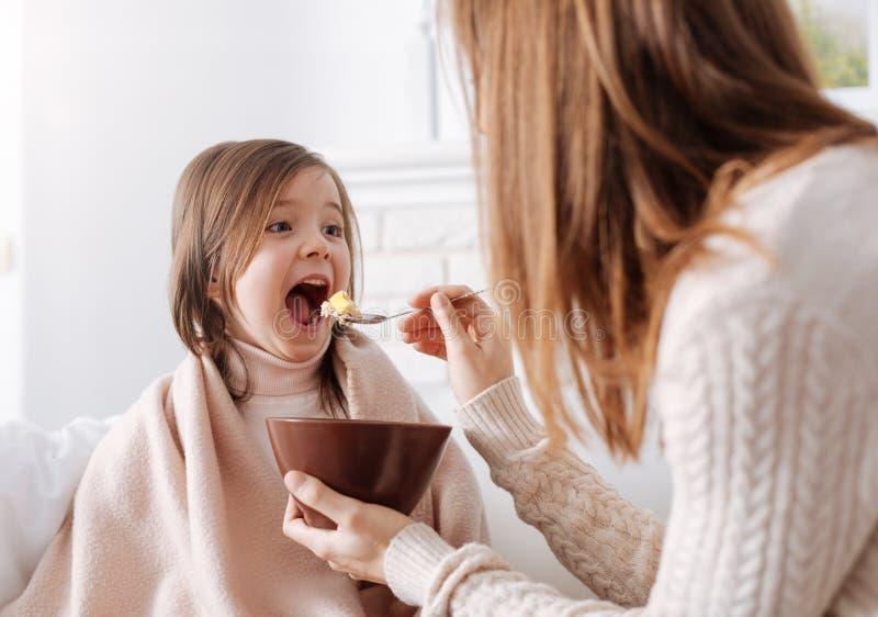 Bambina positiva che gode della sua prima colazione con la madre immagine stock libera da diritti