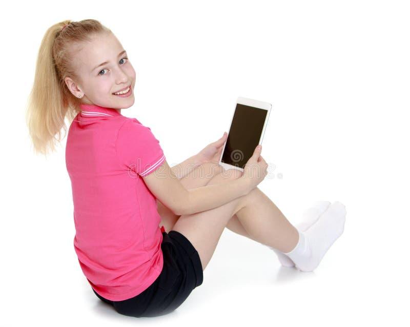 Bambina positiva che si siede sul pavimento fotografie stock