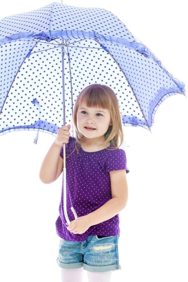Bambina positiva che sta sotto un blu immagine stock libera da diritti