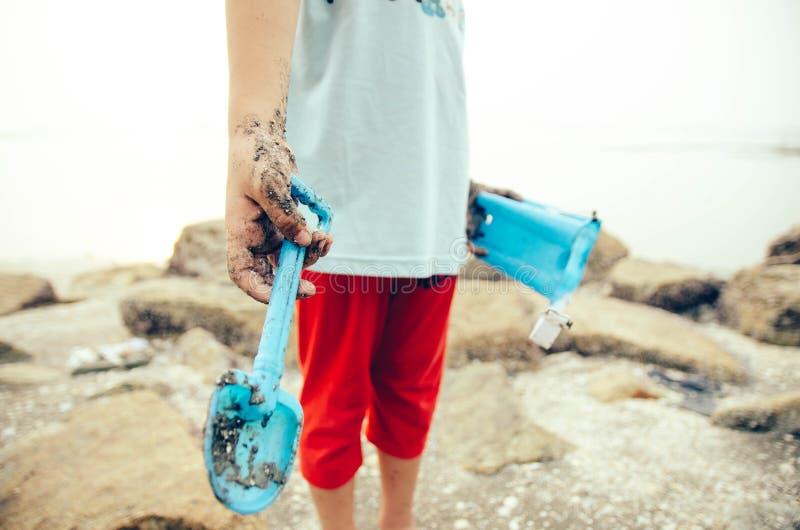 Bambina potata di immagine con la mano fangosa, stante sulla roccia immagine stock libera da diritti