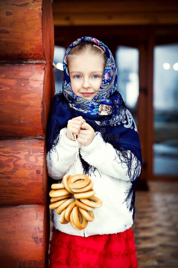Bambina russa in uno scialle blu sul portico della casa fotografie stock