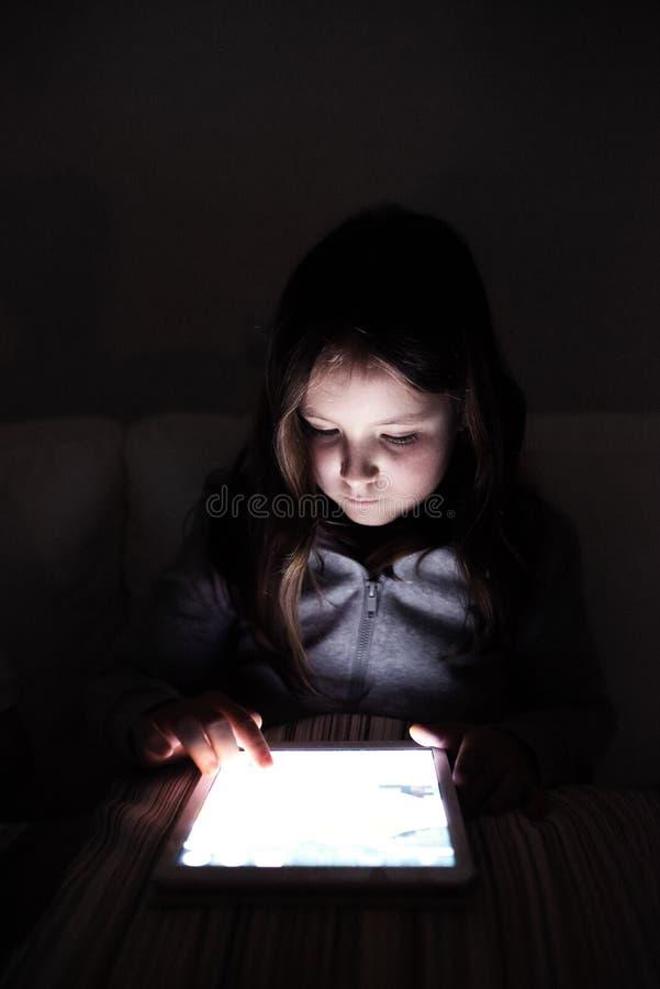 Bambina, sedendosi in uno scuro, giocando con la compressa immagini stock libere da diritti