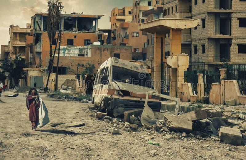 Bambina senza tetto che cammina nella città distrutta immagine stock