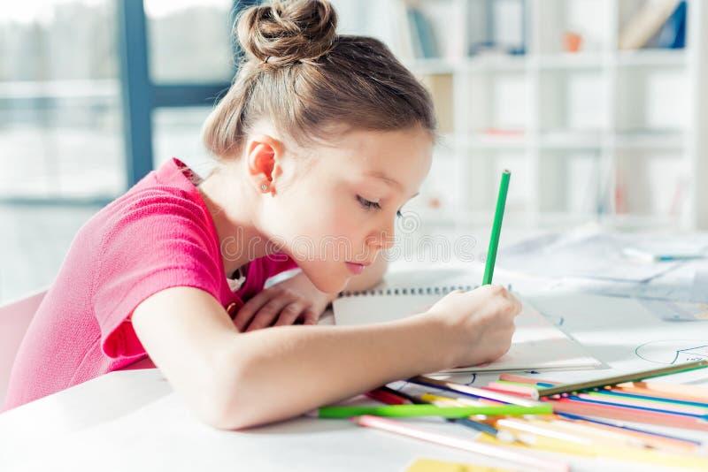 Bambina seria adorabile che si siede alla tavola ed al disegno fotografie stock