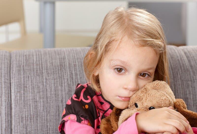 Bambina sola che si siede tristemente sul sofà fotografie stock