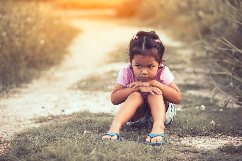 Bambina sola e triste che si siede nel parco fotografia stock