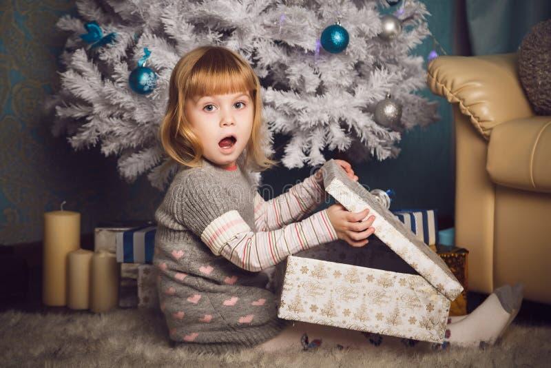 Bambina sorpresa con il grande presente vicino all'albero di Natale fotografia stock