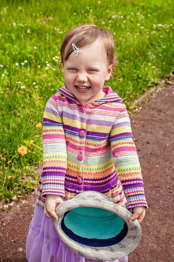 Bambina sorridente all'aperto che tiene cappello immagini stock