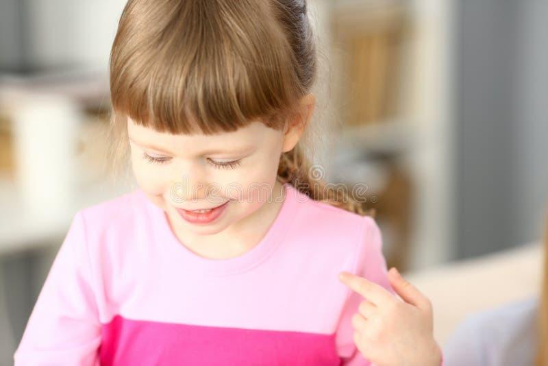 Bambina sorridente che fa qualche cosa di interessante mentre giocando fotografia stock