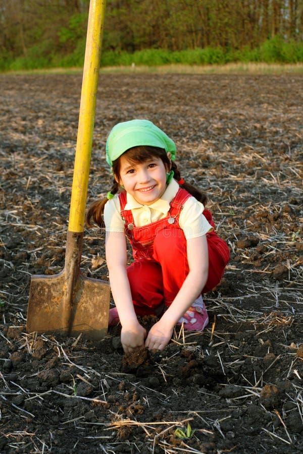 Bambina sorridente che si siede sul campo con la pala immagine stock libera da diritti