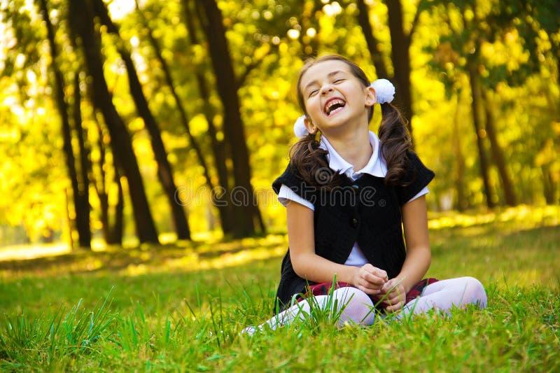 Bambina sorridente che si siede sull'erba immagine stock