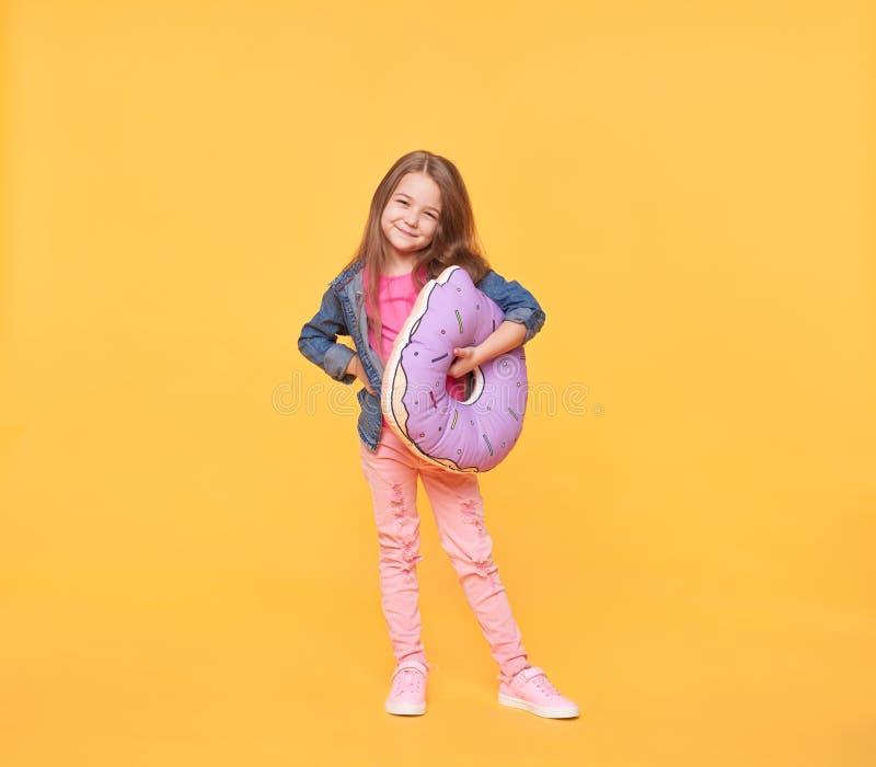 Bambina sorridente che tiene un cuscino gigante della ciambella fotografia stock libera da diritti