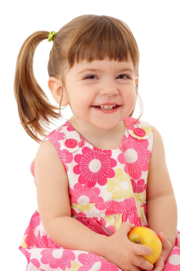 Bambina sorridente con la mela gialla fotografia stock