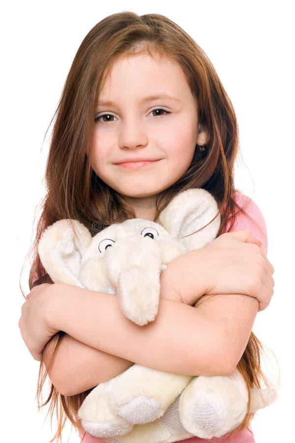 Bambina sorridente con un elefante dell'orsacchiotto fotografie stock