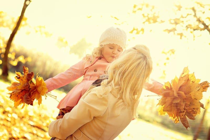 Bambina sorridente della tenuta della donna con le foglie di autunno fotografia stock