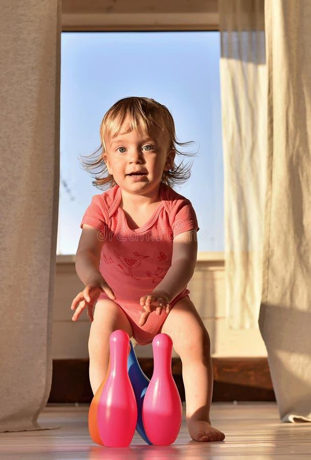 Bambina sorridente felice che gioca bowling con i perni colorati fotografia stock
