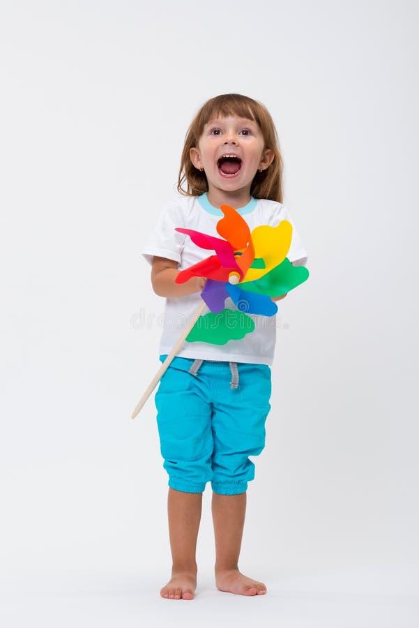 Bambina sorridente felice che giudica un mulino a vento variopinto della girandola del giocattolo isolato su fondo bianco fotografia stock