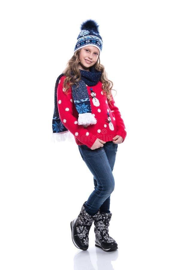 Bambina sorridente graziosa con l'acconciatura riccia che porta maglione, sciarpa e cappello tricottati con i pattini isolati su  immagini stock