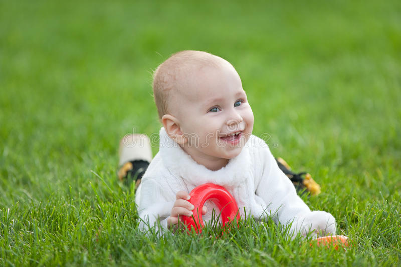 Bambina sorridente nel bianco su erba verde fotografie stock libere da diritti