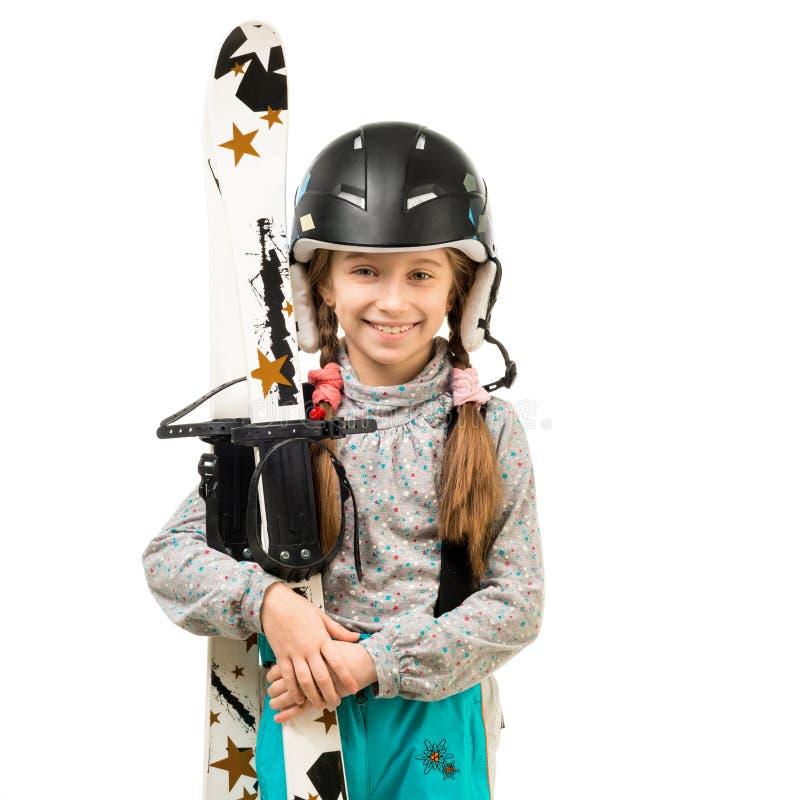 Bambina sorridente in sci della tenuta del casco fotografie stock libere da diritti