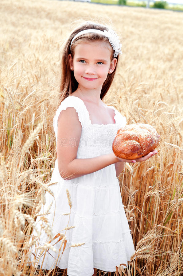 Bambina sorridente sul campo di grano immagini stock