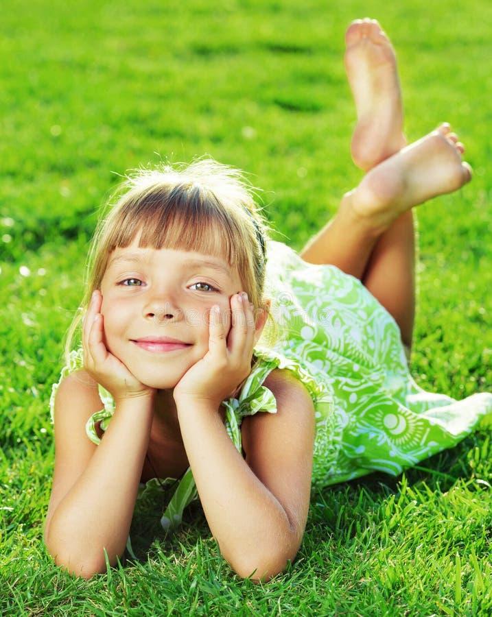 Bambina sorridente sveglia che si trova su un'erba verde nel parco sulla a immagini stock libere da diritti