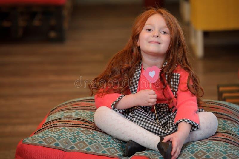 Bambina sorridente sveglia che tiene giocattolo a forma di labbra con cuore immagini stock libere da diritti
