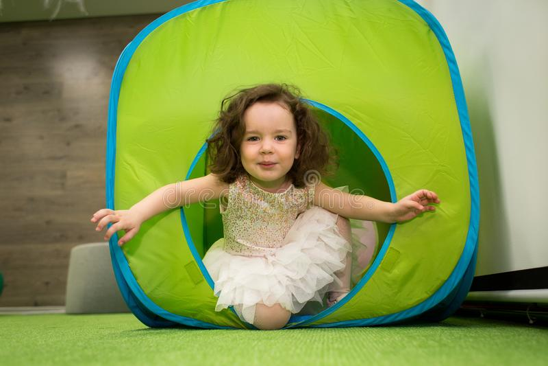 Bambina striscia nel tunnel giocattolo durante la festa dei bambini immagini stock