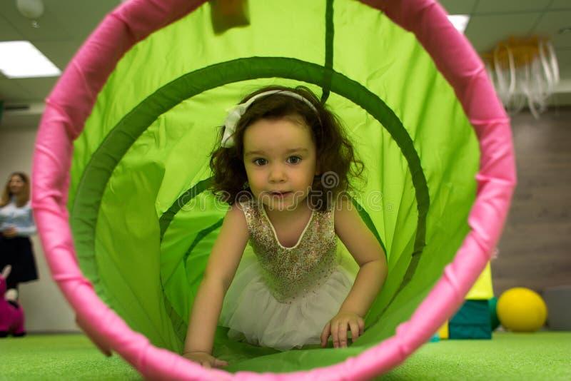 Bambina striscia nel tunnel giocattolo durante la festa dei bambini fotografie stock