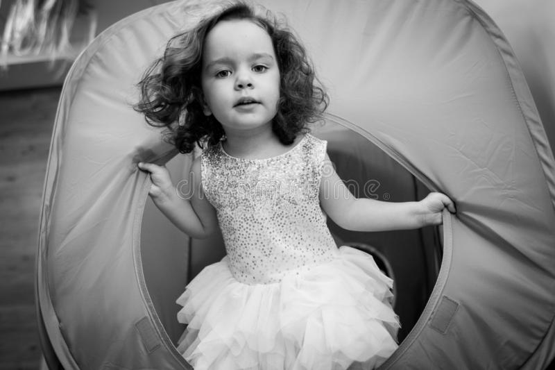 Bambina striscia nel tunnel giocattolo durante la festa dei bambini Foto in bianco e nero immagini stock