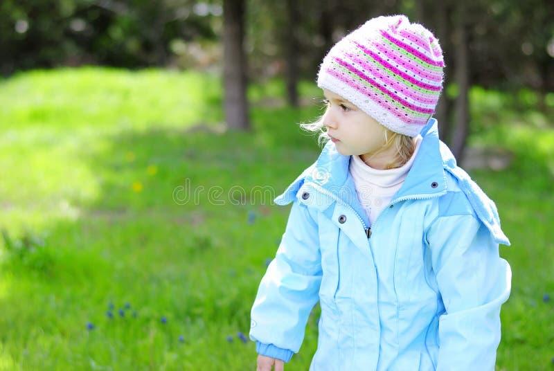 Bambina su erba verde in primavera nel parco per una passeggiata immagine stock libera da diritti