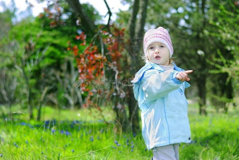 Bambina su erba verde in primavera nel parco per una passeggiata immagine stock