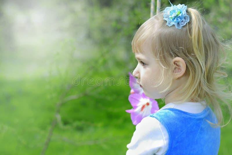 Bambina su erba verde in primavera in un vestito blu fotografie stock libere da diritti