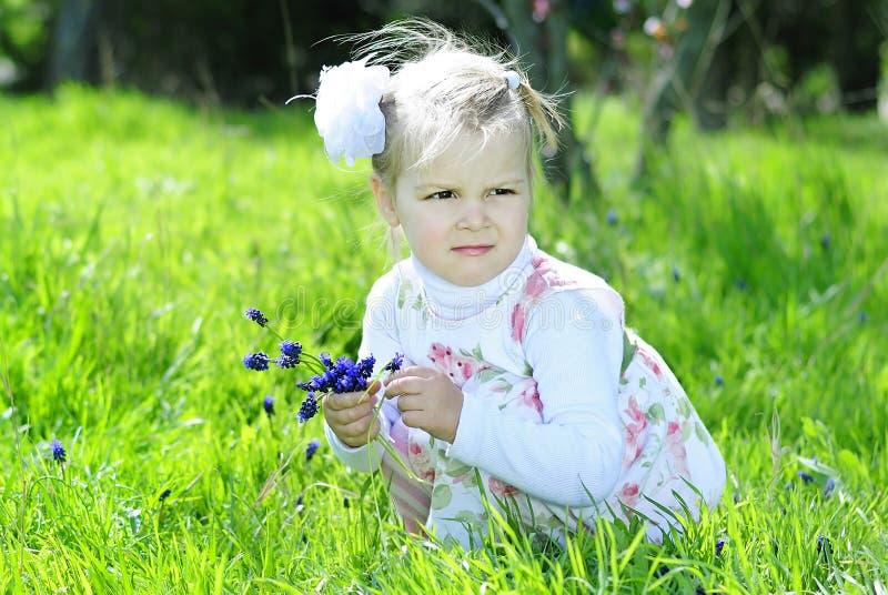 Bambina su un prato verde in un bello vestito immagini stock