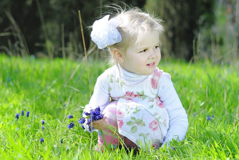 Bambina su un prato verde in un bello vestito fotografia stock