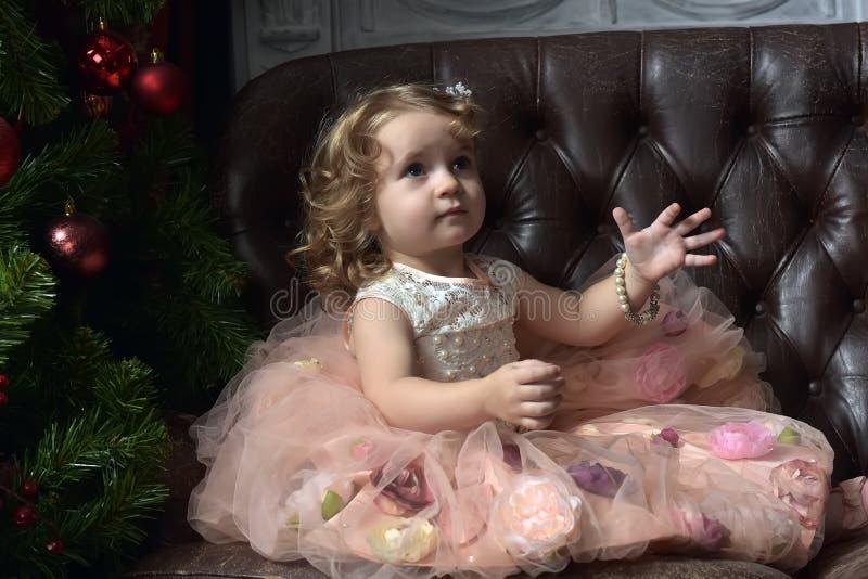 Bambina su un sofà di cuoio a natale fotografie stock