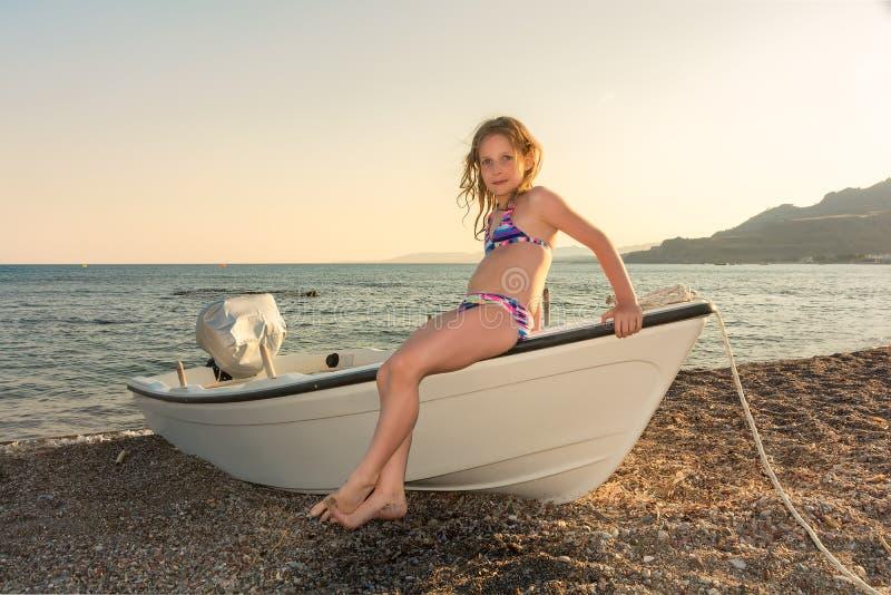Bambina su una barca dalla spiaggia al tramonto fotografie stock