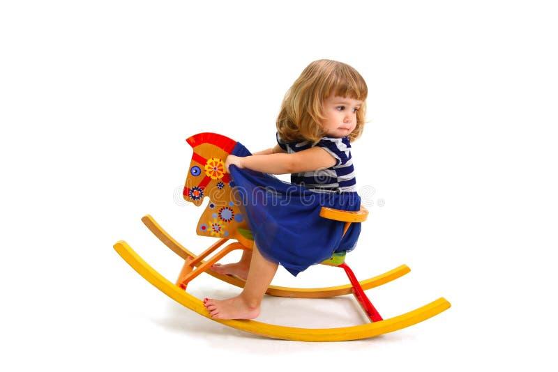 Bambina sul cavallo di legno del giocattolo su fondo bianco fotografie stock