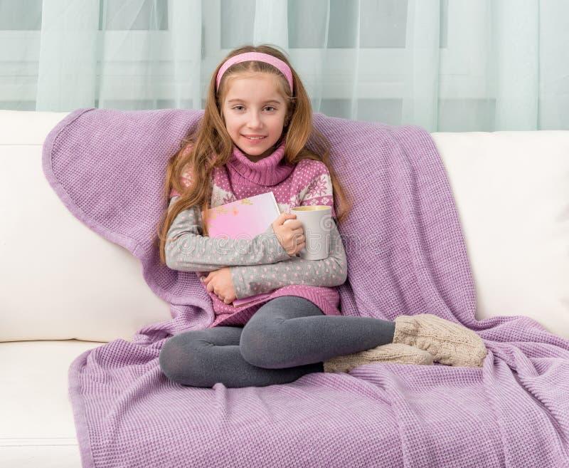 Bambina sul sofà con il libro immagini stock libere da diritti