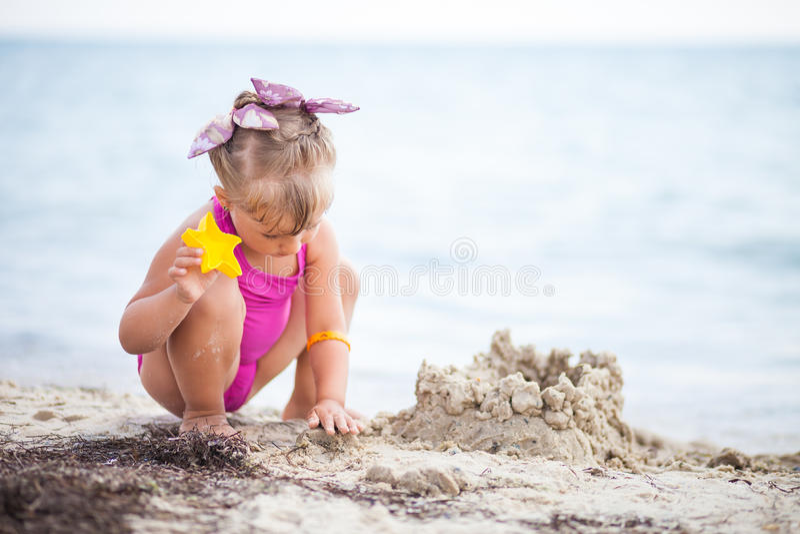 Bambina sulla spiaggia che costruisce un castello della sabbia immagine stock
